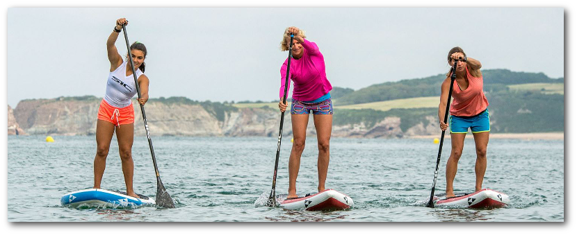 Three lady friends paddle boarding together.