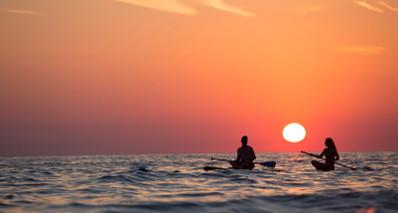 Couple enjoying sunset on their paddle board.